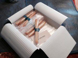 Gebäckröllchen, einzeln verpackt in Plastik, geschützt mit Luftpolsterfolie und Wellpappe, Umverpackung aus Metall
